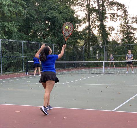 Girl serving tennis ball.